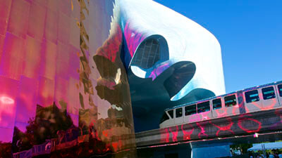 Seattle Monorail Emerging from the EMP Museum by Les Williams is licensed under CC BY-SA 2.0